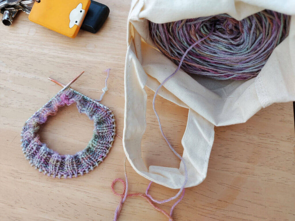 The start of a sock cuff is on a short circular needle and the rest of the pastel yarn cake is inside a cream fabric bag with handles. To the top left are car keys with an orange Herdy key ring.