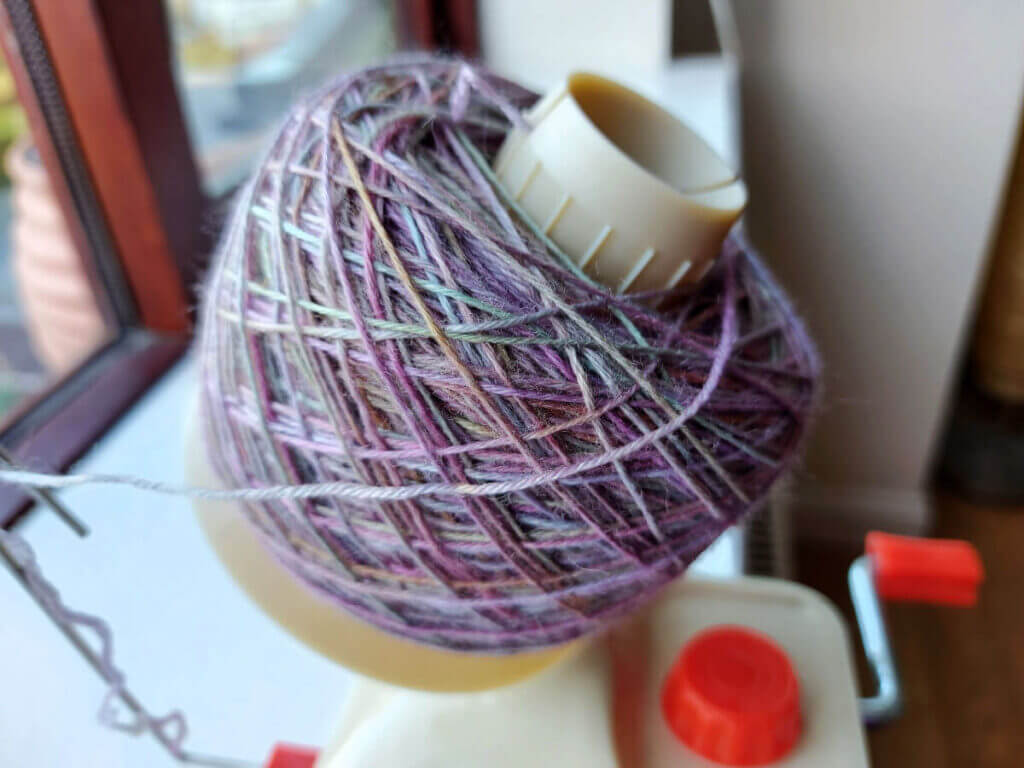 A large yarn cake is on the winder and all the yarn is used up.