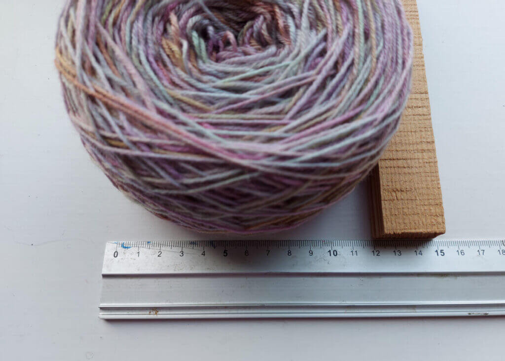 The yarn cake sits against a metal ruler and a piece of wood shows where the edge of the cake reaches to - 12 cm