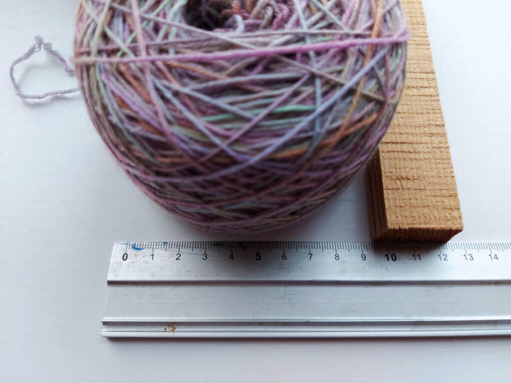 The yarn cake sits against a metal ruler and a piece of wood shows where the edge of the cake reaches to - 9.5cm