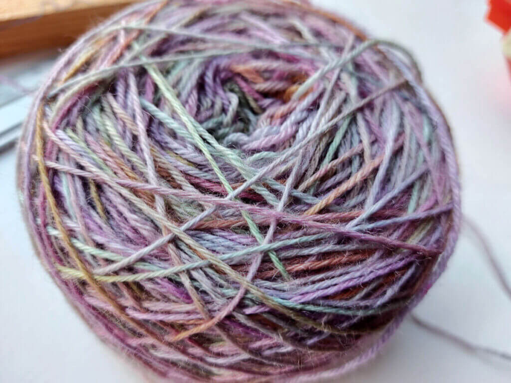 A photo of the pastel coloured yarn cake from above. Some of the yarn looks thinner as it has been pulled tighter across the cake.