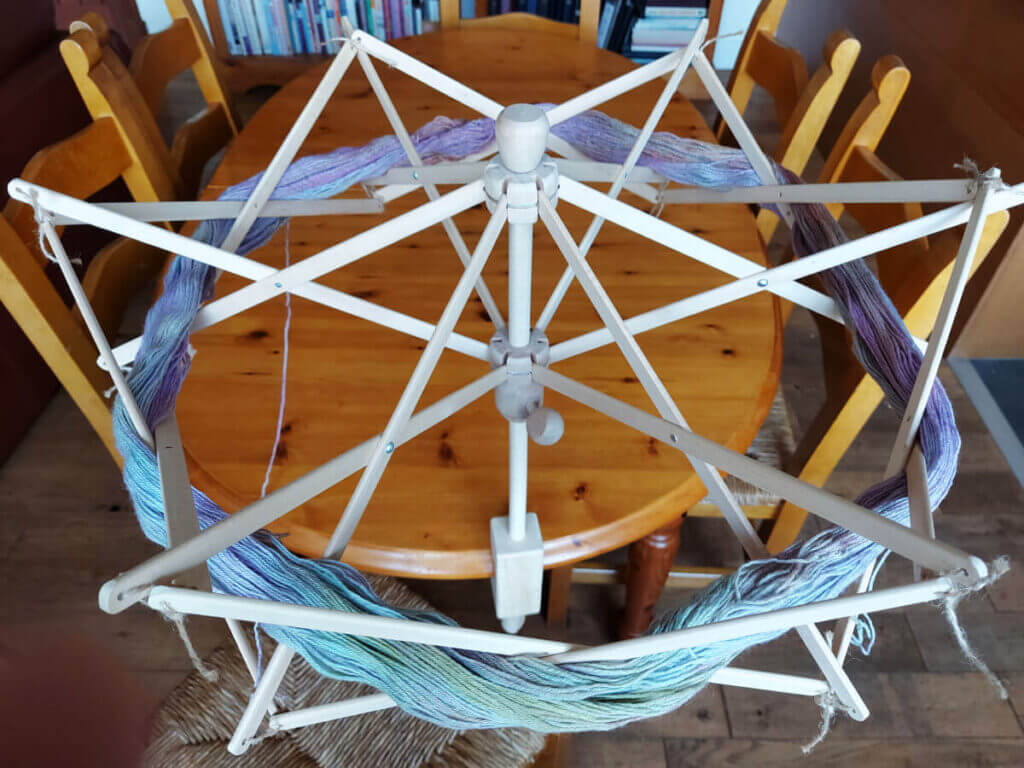 A skein of pastel coloured yarn opened up and draped around a wooden umbrella swift. The ribs of the swift hold the yarn safely whilst it turns. The swift is attached to a pine dining table. There are chairs around the table and bookcases in the background.
