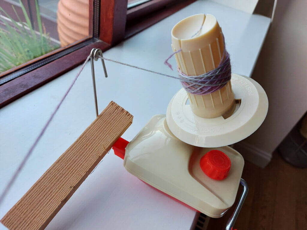 A red and cream yarn winder attached to a window sill. A piece of wood stops the guide falling over and there is a small amount of yarn wound onto it.